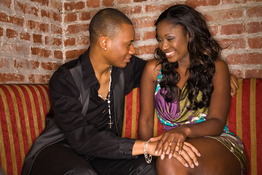 """""""A young couple seated in the corner of a club flirting. Emotion is close, intimate and he is leaning in and she is happy and responsive to his advance."""""""